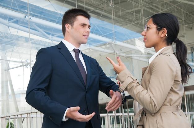 深刻なビジネス人々が身振りで示し、屋外で問題を議論