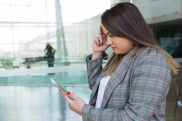 深刻なビジネスの女性を考えて屋外でタブレットを使用して