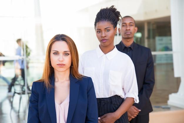 Серьезные уверенные деловые люди, стоящие в ряду