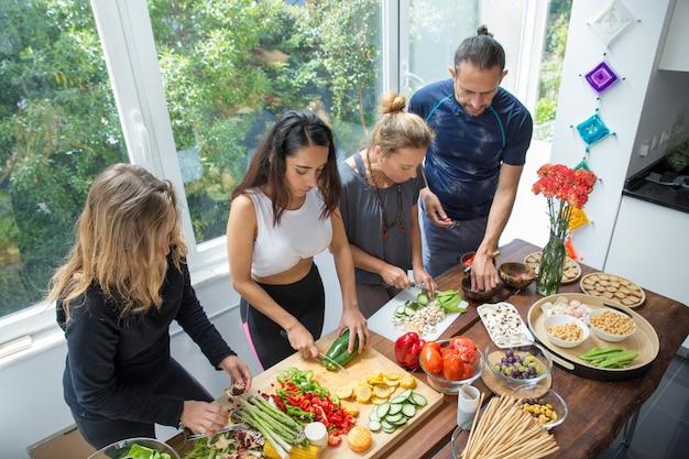 深刻な人々が台所のテーブルで野菜を料理