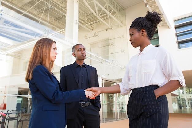 Серьезные строгие бизнес-леди пожимают друг другу руки в офисе