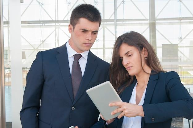 深刻な女性がタブレットに集中男性データを表示