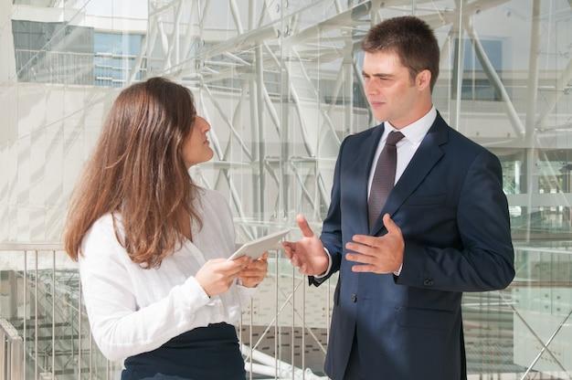 深刻な女性がタブレット上の男性データを表示、プロジェクトについて議論します。