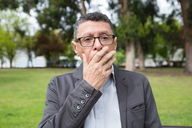 Шокированный мужчина средних лет прикрывает рот рукой в парке