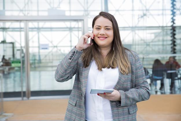 スマートフォンを屋外で呼び出すビジネス女性の笑みを浮かべてください。