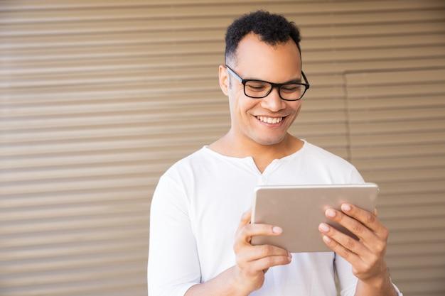 タブレットに取り組んでいる若い混血男の笑みを浮かべてください。正面図