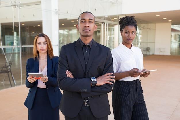 Успешная бизнес-команда позирует в офисном зале