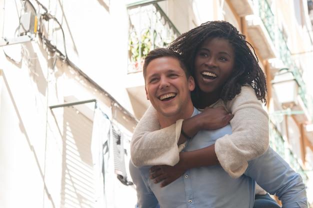 笑いと屋外の背中にガールフレンドを運ぶ若い男
