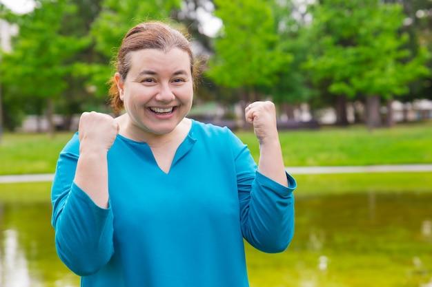 幸せな興奮プラスサイズの女性の成功を祝う