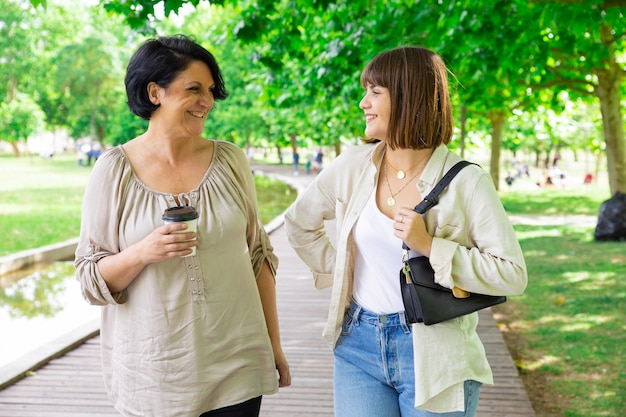幸せな若い女性と彼女の母親はチャットと公園を散歩して