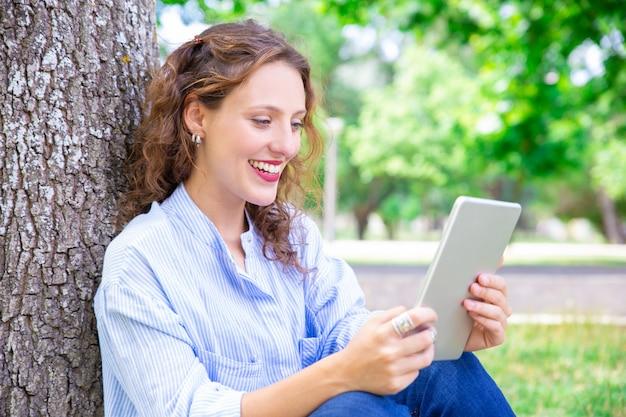 Счастливая молодая женщина, говорить через приложение телекоммуникаций на планшете