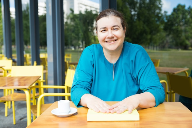 Позитивный учитель пьет кофе в кафе колледжа