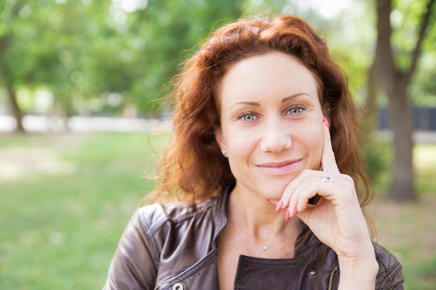 笑顔の女性の顔に触れると都市公園でカメラにポーズ