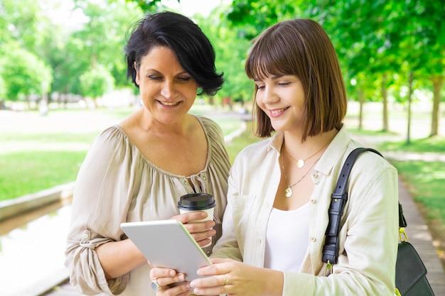 若い女性と彼女の母親が公園でタブレットを使用して笑顔