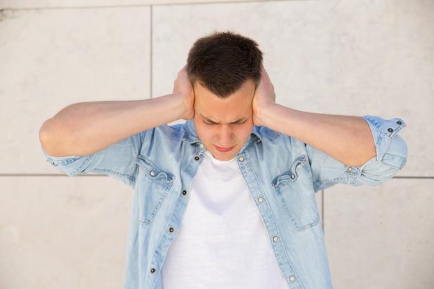 屋外の壁で手で耳を覆う腹が立つ若い男
