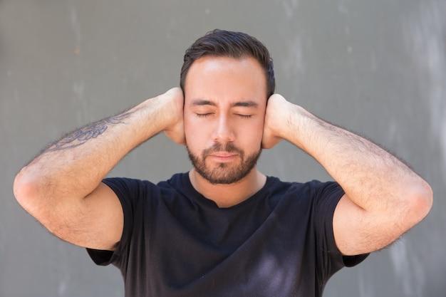 ひげを生やした若い男の手で耳を閉じる