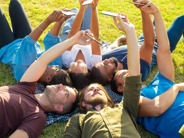 Веселый друг лежит и использует смартфоны