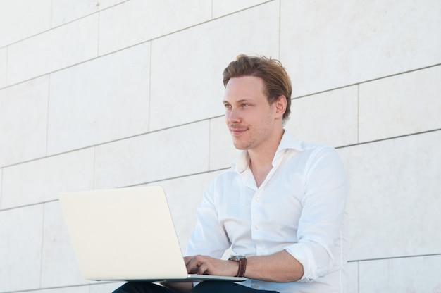 屋外のラップトップに取り組んで幸せなビジネスの男性