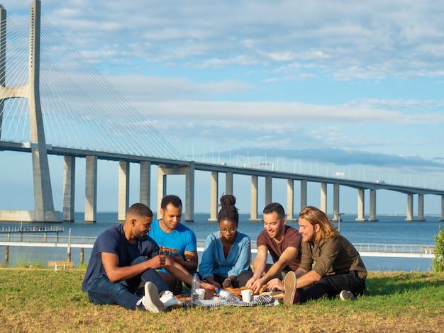 公園でピクニックを持つ友達に笑顔