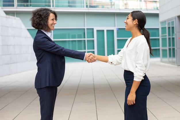 事務所ビルの近くで握手する陽気な同僚。フォーマルなスーツを着た若い女性が屋外会議。ビジネスハンドシェイクコンセプト