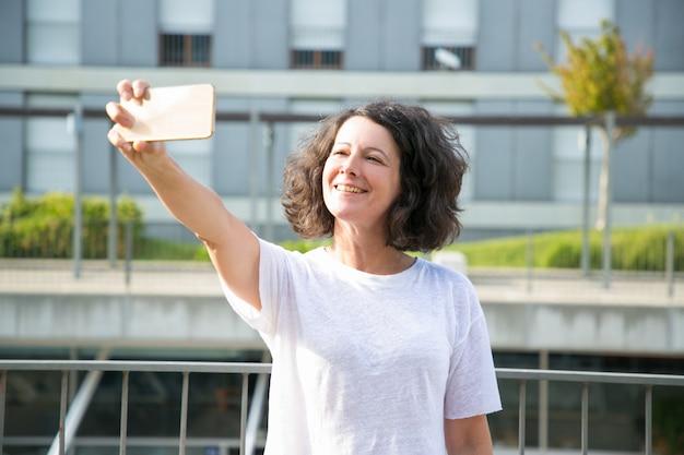 Веселая женщина турист, принимая селфи