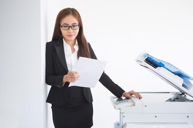 コピー機でのコンテンツのアジア女性アシスタント立ち