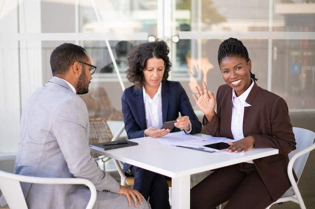 こんにちはを振って幸せなアフリカ系アメリカ人ビジネス女性