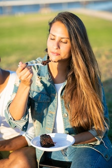 公園でおいしいケーキを食べてリラックスした白人女性。プラスチック製の皿からケーキを食べて公園に座っている陽気な若者。余暇