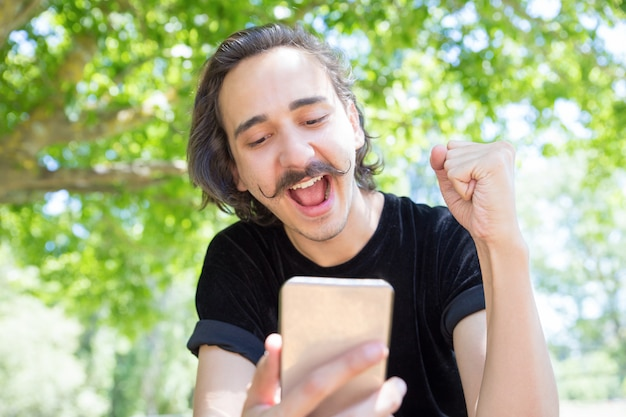 Счастливый молодой человек, глядя на смартфон в парке.