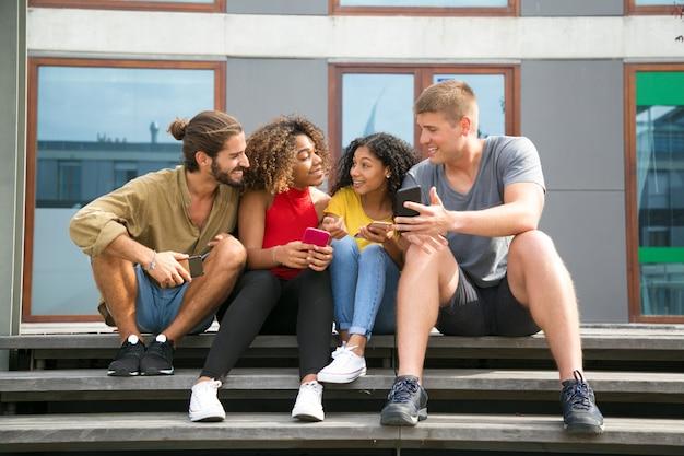 Счастливые веселые друзья читают новости на экранах телефонов
