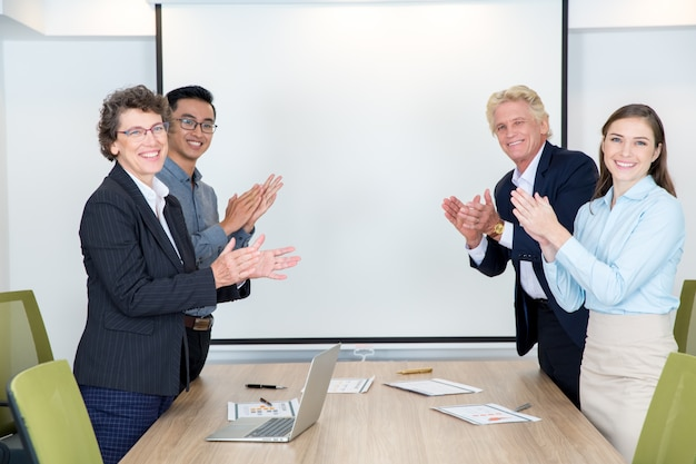 Четыре партнеры аплодируют в зале заседаний