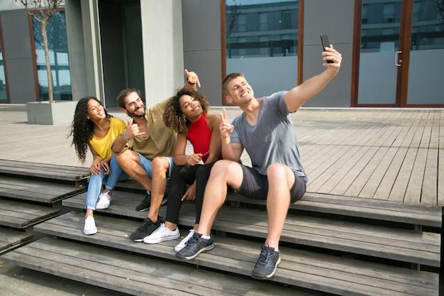 Счастливые многонациональные студенты, принимающие селфи