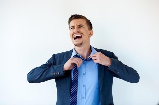 Разочарованный бизнесмен развязывая галстук и крика