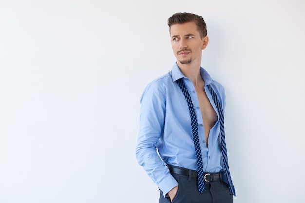 Задумчивый привлекательный бизнесмен в расстегнутой рубашке