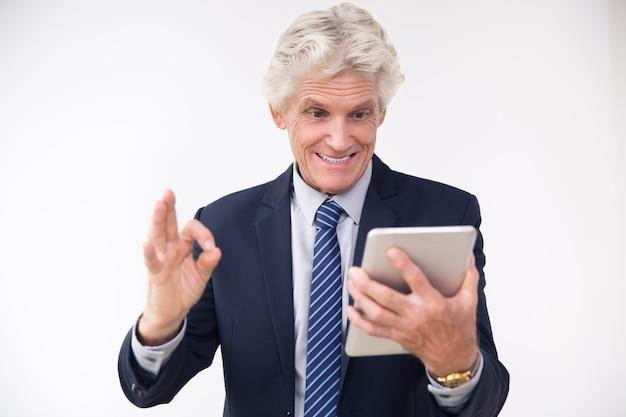 Возбужденные старший бизнесмен, глядя на сенсорной панели