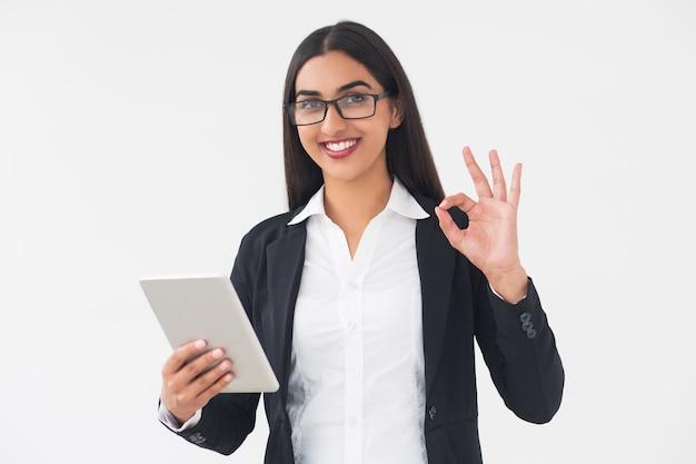 Улыбаясь элегантная женщина с планшетного показаны знак ок