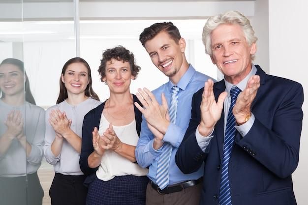 Успешные деловые люди улыбаются и аплодируют