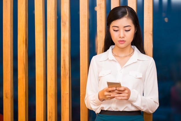 Крупным планом довольно азии брюнетка с использованием смартфон