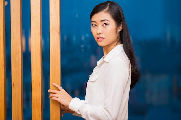 木製パーティションでプリティアジアの女性のクローズアップ