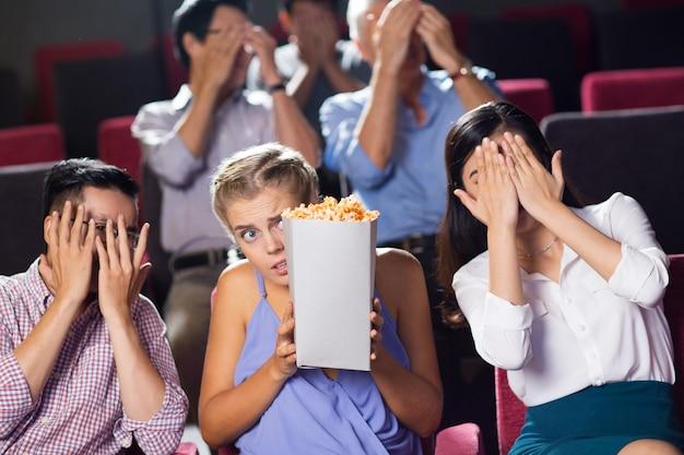 映画館でホラー映画を見ておびえる友人