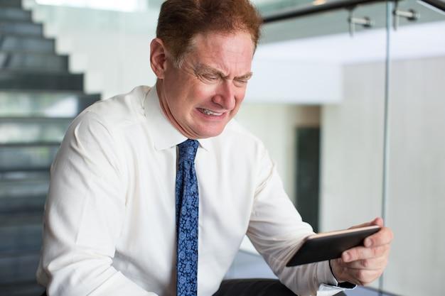 電話でメッセージを読む怒っている高齢者のビジネスマン