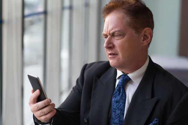 Недовольный старший менеджер, читая сообщение по телефону