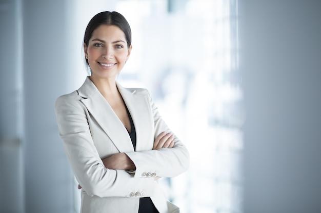 Улыбаясь женщина бизнес-лидера с оружием, пересекли