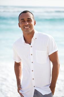ビーチでカメラを見ている笑顔のハンサムな男