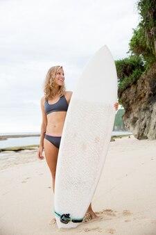 サーフボードでビーチに立つ美しい女性