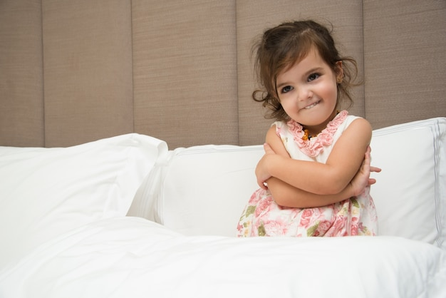 Забавная маленькая девочка, обнимая себя в постели