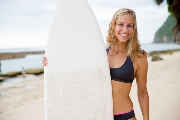 ビーチでサーフボードで立っている幸せな女性