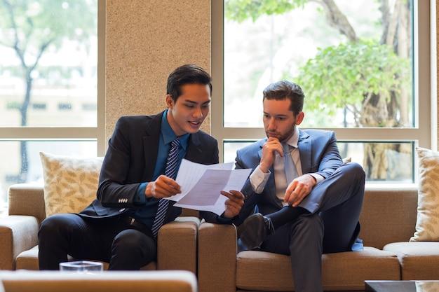Два бизнесмена обсуждают документ в зале ожидания