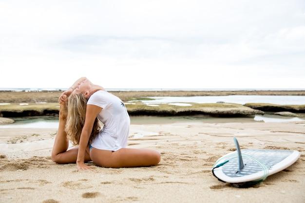 ビーチでサーフボードで体を伸ばしている女性