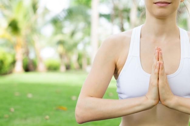 屋外でヨガを練習する若い白人の女性